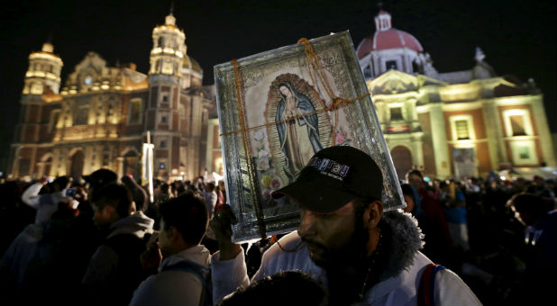 A pilgrim holds up an image of the Virgin of Guadalupe at the Basilica of Guadalupe during the annual pilgrimage in honor of the Virgin of Guadalupe, in Mexico City.