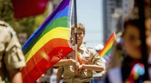 A Boy Scout holds a gay flag.