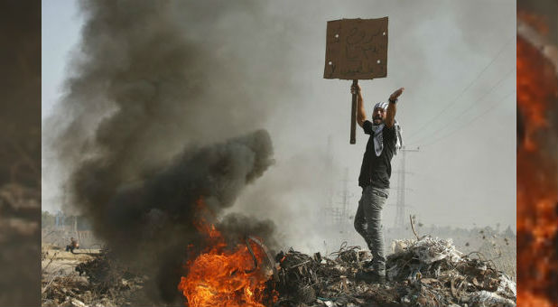"A Palestinian protester shouts during clashes with Israeli troops. In a recent attack, an elderly woman was saved by proclaiming the name of ""Jesus"" while Palestinian terrorists stabbed her."