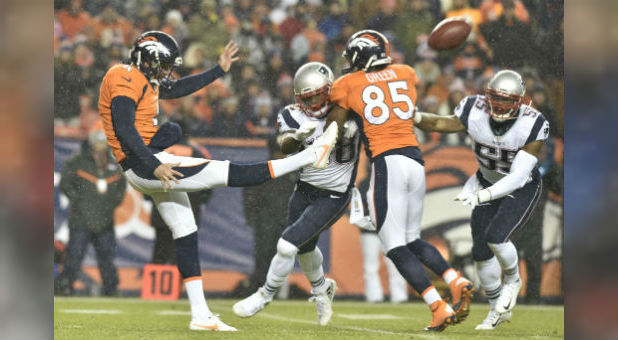 Denver Broncos punter Britton Colquitt (4) punts while Virgil Green blocks against the New England Patriots. Both players have faith in Jesus Christ.