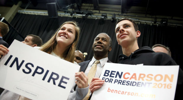 Republican U.S. presidential candidate Ben Carson takes a photo with Claire Birchmier, 17, and Brandon Short, 18, both of Carlisle, Iowa, after speaking at a Trust in God town hall at Simpson College in Indianola, Iowa.