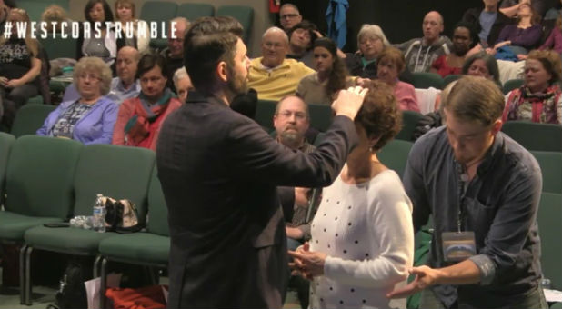 "Charlie Shamp prays over a woman March 3 at the Seattle Revival Center. The man in back of her is known as a ""catcher"" in case she falls to the ground."