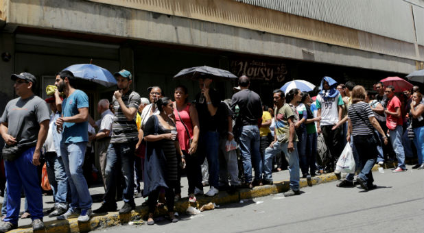 People queue to try to buy basic food items outside a supermarket in Caracas, Venezuela, last month.