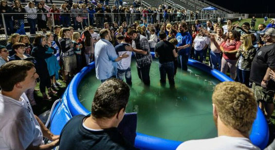 Hundreds of students have recently accepted Christ. Here, students are baptized in an inflatable pool inside the Mingo Central's football stadium.