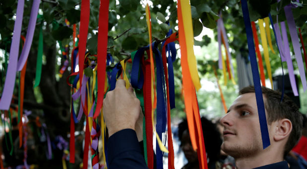 "A man ties ribbons to the ""Survivor Tree"" for the victims of the mass shooting in an Orlando nightclub during a public tribute to the victims"