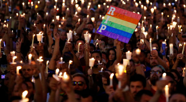eople take part in a candlelight memorial service the day after a mass shooting at the Pulse gay nightclub in Orlando