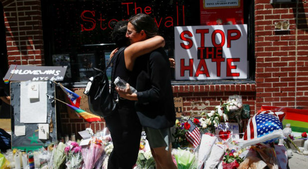 Matti Mejia (L) and Shaina Roberts embrace after laying flowers at a memorial outside The Stonewall Inn in New York.
