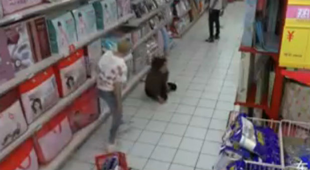 A woman who appears possessed collapsed on the floor of a supermarket.