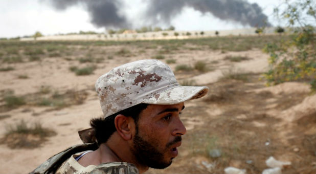 A member of the Libyan forces allied with the U.N.-backed government looks at Islamic State fighters' positions during a battle in Sirte.