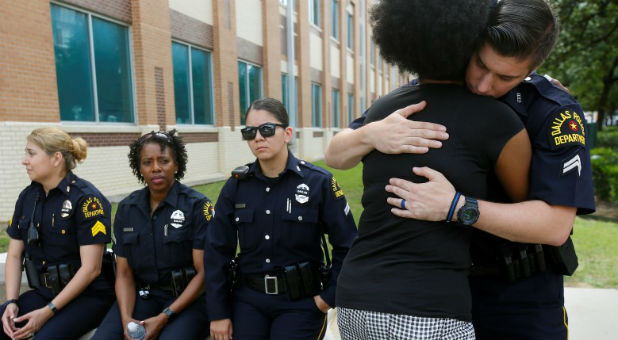 A Supporter Hugs A Dallas Police Officer At A Makeshift Memorial At Police  Headquarters Following The