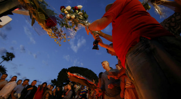 People gather to leave flowers in tribute to victims the day after a truck ran into a crowd at high speed killing scores and injuring more on the Promenade des Anglais who were celebrating the Bastille Day national holiday, in Nice, France
