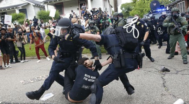Police scuffle with a demonstrator as they try to apprehend him during a rally in Baton Rouge, Louisiana U.S.