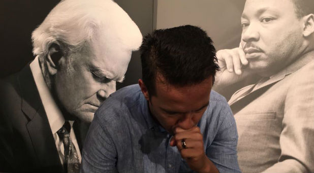 Rev. Samuel Rodriguez prays with the images of Billy Graham and Martin Luther King Jr. in the background.