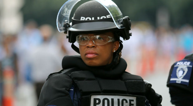 A female police officer wears riot gear as she stands in position outside a football game in Charlotte, North Carolina.
