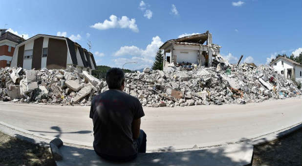 A man sits in front of collapsed houses following an earthquake.