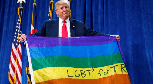 "Republican presidential nominee Donald Trump holds up a rainbow flag with ""LGBTs for TRUMP"" written on it at a campaign rally in Greeley, Colorado"