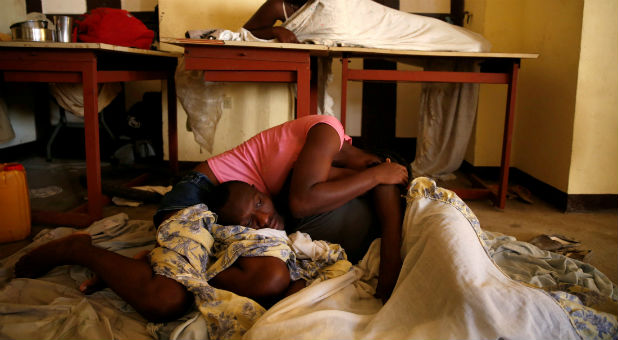 People sleep on the floor in a partially destroyed school used as a shelter after Hurricane Matthew hit Jeremie, Haiti