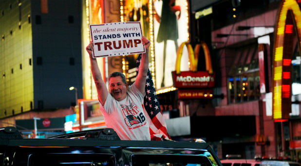 A man leans out of a Hummer shouting words in support of U.S. Republican presidential nominee Donald Trump while driving through Times Square in New York