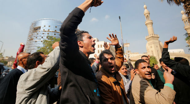 Egyptian Christians react and shout slogans as ambulances transport the bodies of victims killed in the bombing of Cairo's main Coptic cathedral after the funeral, in Cairo, Egypt.
