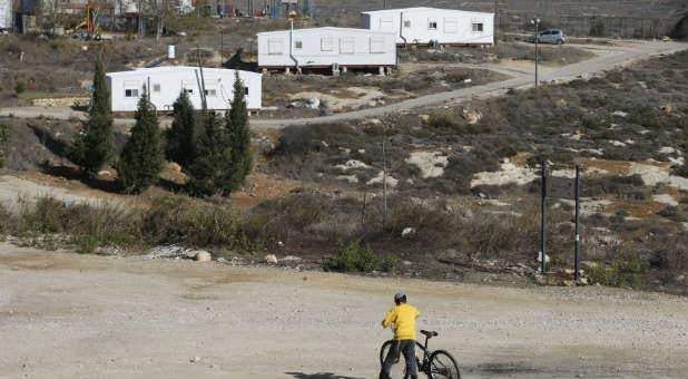 An Israeli boy holds his bicycle near homes in the Jewish settler outpost of Amona in the West Bank.