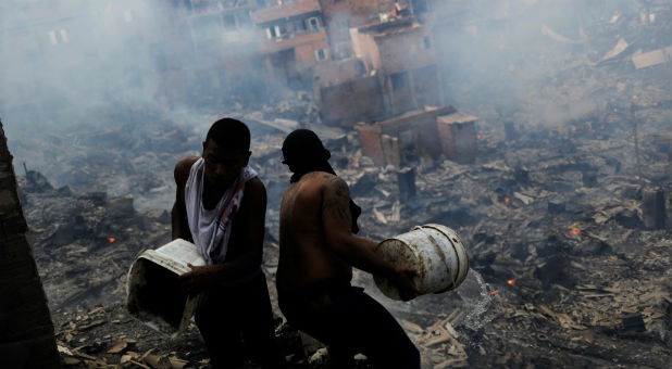 Residents pour water from their houses as they try to extinguish a fire at Paraisopolis slum in Sao Paulo, Brazil