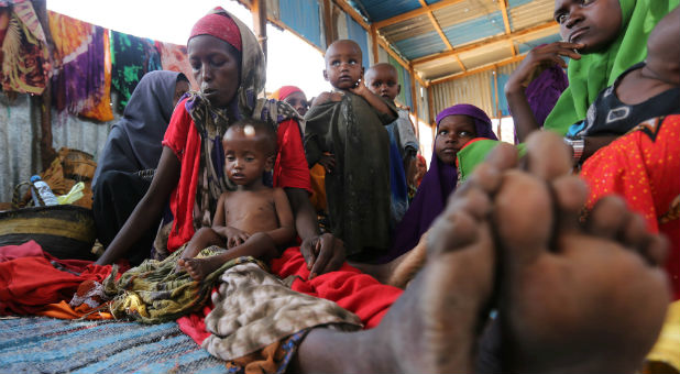 An internally displaced Somali woman sits with her children inside their general shelter at the Al-cadaala camp in Mogadishu.