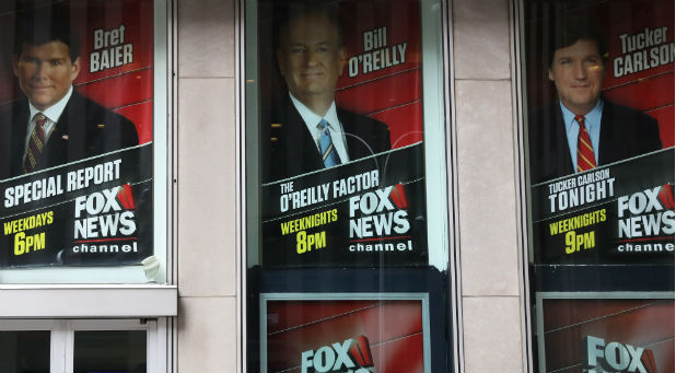 Posters featuring Fox News Channel talent including TV anchor Bill O'Reilly are seen outside the News Corporation headquarters in New York City