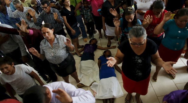 People pray during a mass in an evangelical church in the village of Rio Pardo next to Bom Futuro National Forest, in the district of Porto Velho, Rondonia State, Brazil