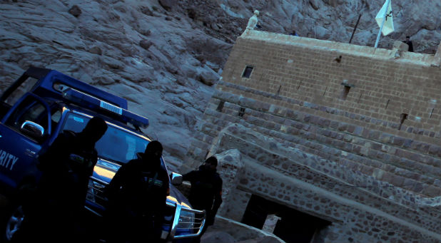 Special police forces stand guard as a Greek monk is seen on the top of a church at Saint Catherine's monastery, in the Sinai Peninsula, south of Egypt, in this file photo taken December 8, 2015.