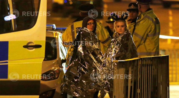 Two women wrapped in thermal blankets stand near the Manchester Arena, where U.S. singer Ariana Grande had been performing, in Manchester, northern England, Britain, on May 23, 2017.