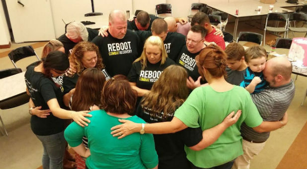 A group of REBOOT members pray together.