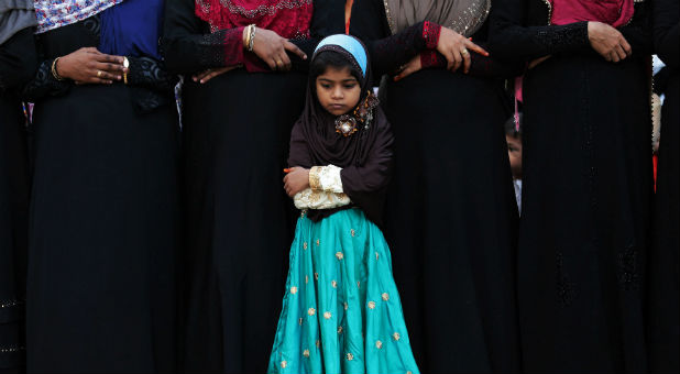 A Muslim girl offers Eid al-Fitr prayers inside a school to mark the end of the holy fasting month of Ramadan.
