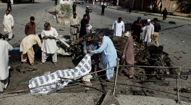 Police and rescue officials cover a body after a blast in Quetta, Pakistan.