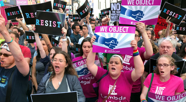 Crowds of people protest President Donald Trump's announcement that he plans to reinstate a ban on transgender individuals from serving in any capacity in the U.S. military, in Times Square, New York.