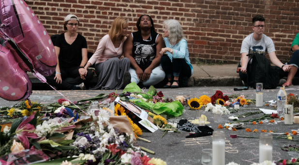 "Women sit by an impromptu memorial of flowers commemorating the victims at the scene of the car attack on a group of counter-protesters during the ""Unite the Right"" rally as people continue to react to the weekend violence in Charlottesville, Virginia."
