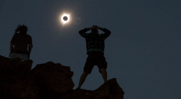 Enthusiasts Tanner Person (R) and Josh Blink, both from Vacaville, California, watch a total solar eclipse while standing atop Carroll Rim Trail at Painted Hills, a unit of the John Day Fossil Beds National Monument, near Mitchell, Oregon, Aug. 21, 2017.