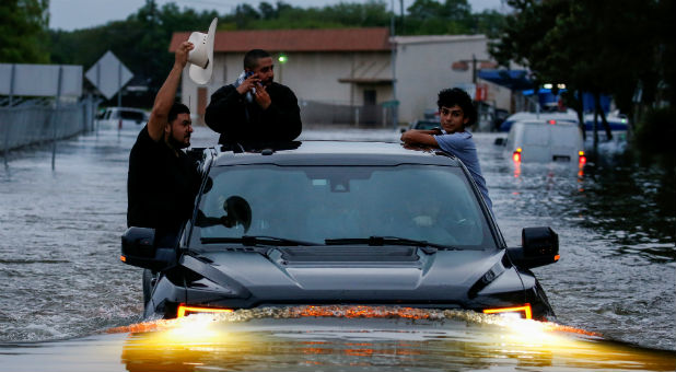 Residents use a truck to navigate through flood waters from Tropical Storm Harvey in Houston, Texas, U.S. Aug. 27, 2017.