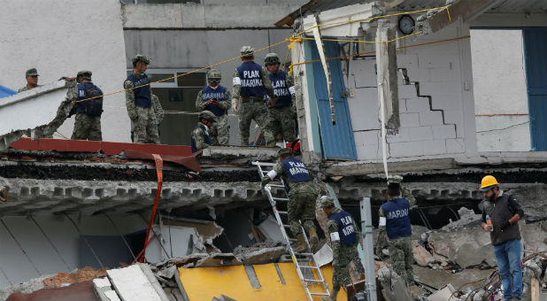 Soldiers search in the rubble of a collapsed building after an earthquake in Mexico City, Mexico.