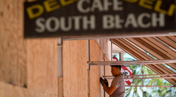 A worker boards up his restaurant in Miami.