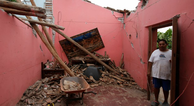 A man stands by his damaged home in Mexico.