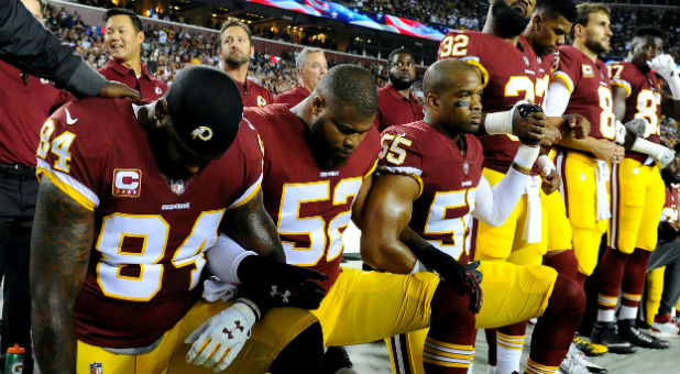 Washington Redskins tight end Niles Paul, linebacker Ryan Anderson and linebacker Chris Carter kneel with teammates.