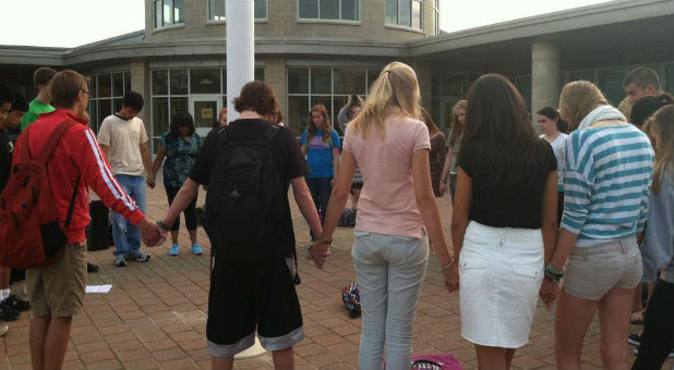 Students gather at the flag pole to pray.