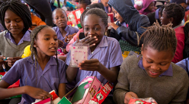 Girls open their Operation Christmas Child shoe boxes.