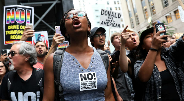 Anti-racism protesters shout during protests in front of Trump Tower.
