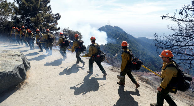 Members of the Los Padres Hot Shot crew walk atop a hill during the Wilson Fire near Mount Wilson in the Angeles National Forest in Los Angeles.