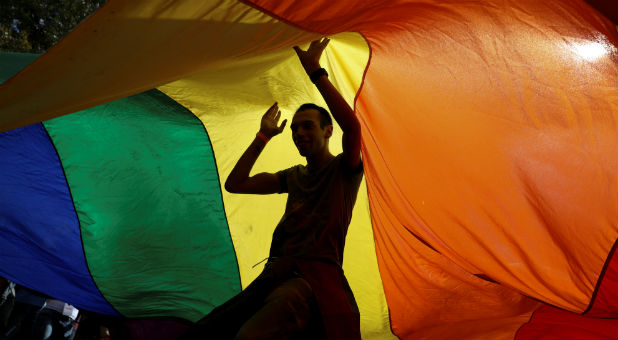 Participants dance under a rainbow flag during an annual LGBT (Lesbian, Gay, Bisexual and Transgender) pride parade.