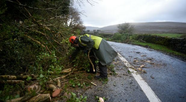 A worker clears fallen trees off a road during Storm Ophelia.