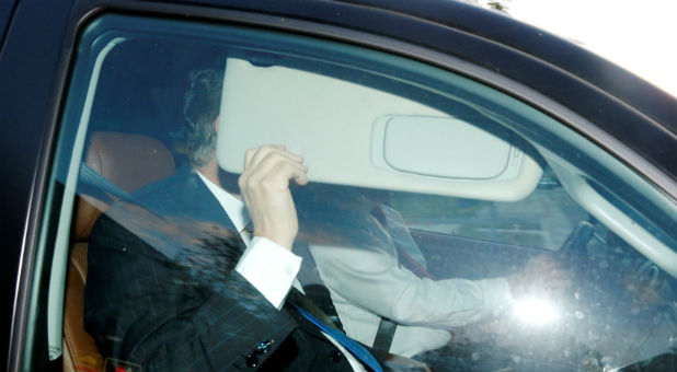 Former Trump campaign manager Paul Manafort hides behind his car visor as he leaves his home in Alexandria, Virginia.