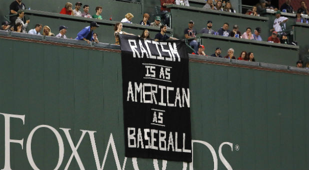 Fans on top of the Green Monster display a racism sign.