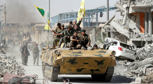 Syrian Democratic Forces (SDF) fighters ride atop of military vehicle as they celebrate victory in Raqqa, Syria.
